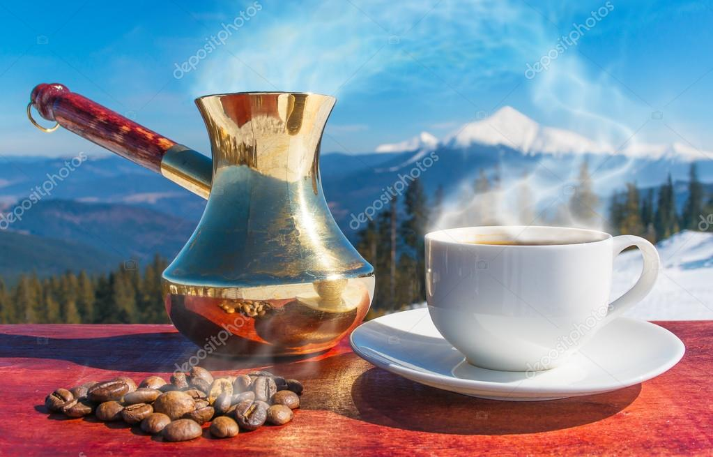 A cup of coffee, coffee beans, coffee mountains in the background.