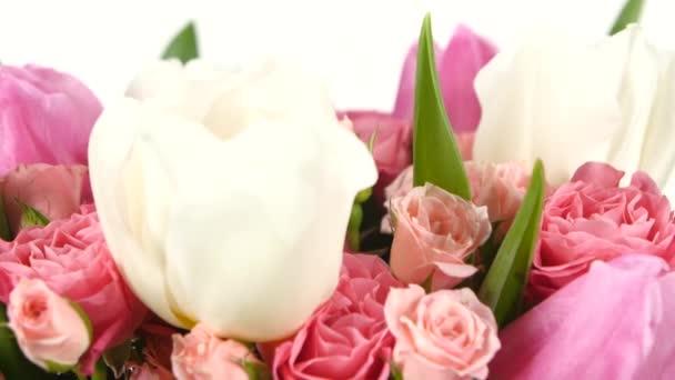 Kytici květin s růžemi a tulipány, na bílé, otáčení, zblízka