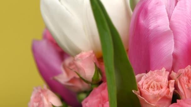 Straně kytici květin s růžemi a tulipány, na žluté, otáčení, zblízka