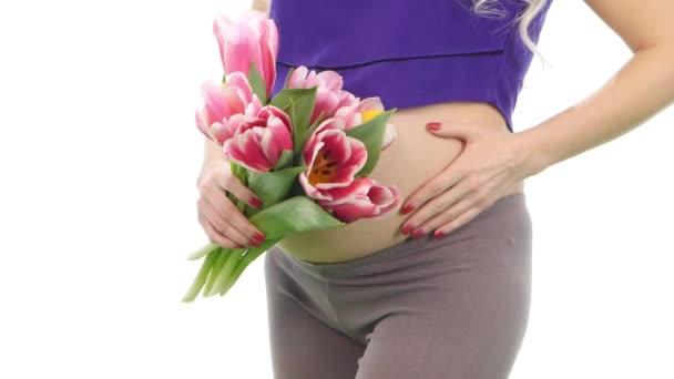Těhotná žena drží její břicho a kytice tulipánů, bílý, záběr