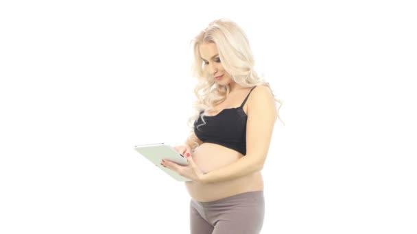 Mladá těhotná žena s tabletem, bílá