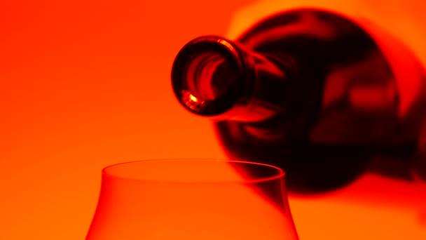Vino rosso che è versato dalla bottiglia al bicchiere, arancione, closeup