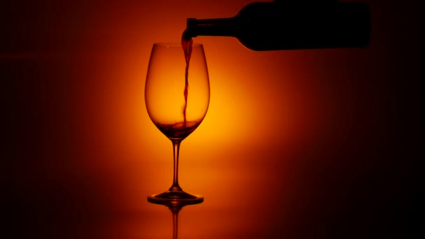 Red wine pouring in glass, dark, slowmotion