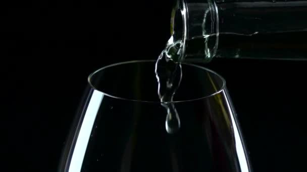 in einem großen Glas Weißwein gegossen, schwarz, Nahaufnahme, Zeitlupe