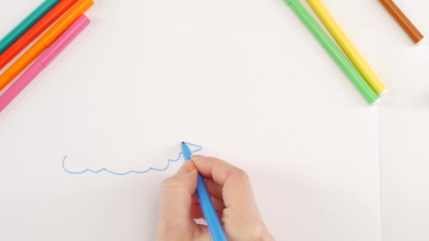 Woman drawing the clouds using blue felt-tip pen on white paper, time lapse