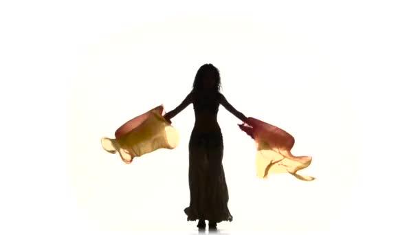 Gyönyörű fiatal egzotikus hastáncos két rajongók, és rázza a csípőjét, a fehér, silhouette, árnyék