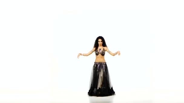 Krásná mladá exotická břišní tanečnice s dlouhými tmavými vlasy, neobvyklé barvy rozkmitá její boky trupu, na bílém pozadí