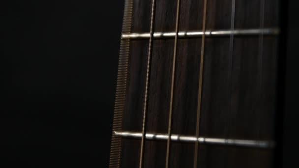 Akustickou kytaru struny, zblízka, Zpomalený pohyb, na černém pozadí