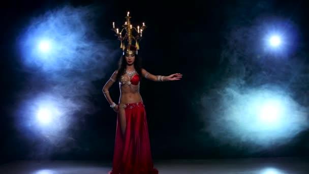 attraktive Bauchtänzerin tanzt weiter mit Kerzen, ihrem Kopf, schwarz, Rauch