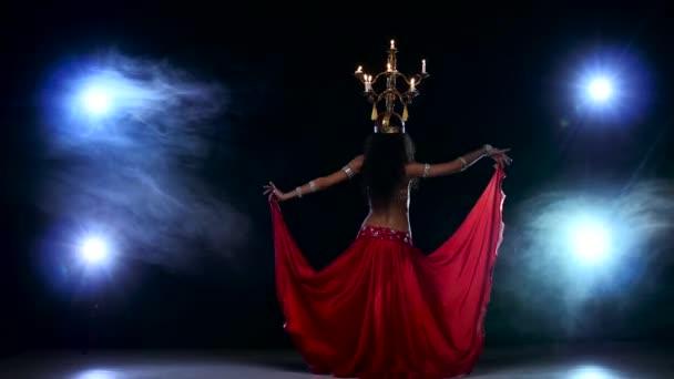 attraktive Bauchtänzerin Mädchen weiter mit Kerzen auf dem Kopf tanzen, schwarz, Rauch