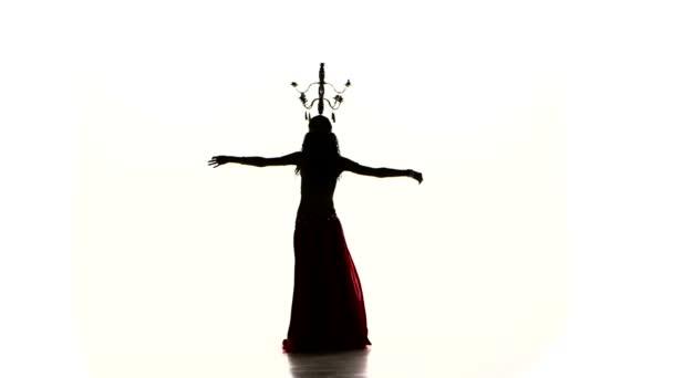 Bauchtänzerin tanzt mit brennenden Kerzen auf dem Kopf, Silhouette, Zeitlupe, auf weiß