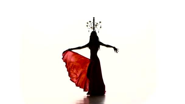 Bauchtänzerin beginnt mit brennenden Kerzen auf dem Kopf zu tanzen, Silhouette, Zeitlupe, auf Weiß