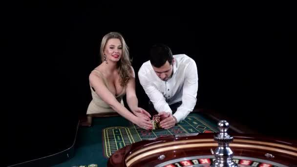 Young man and woman gambling at poker table. Black