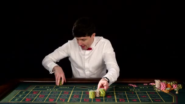Man in a casino playing on the roulette. Black