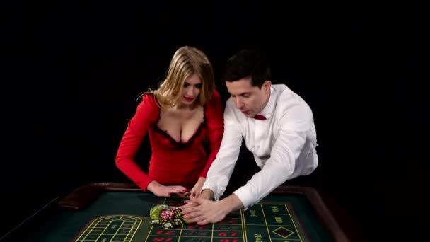 Vyhrává muž a krásná dívka v kasinu. Černé