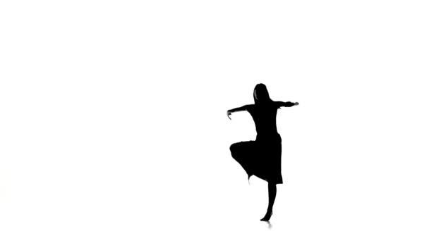 Fiatal nő táncos tánc kortárs tánc és csinál egy split, fehér, sziluett, lassított felvétel