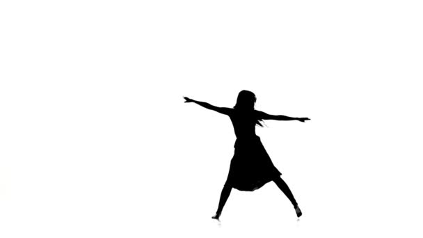 Woman dancer dancing contemporary dance and doing a split, on white, silhouette, slow motion