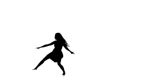 Slim woman dancer dancing contemporary dance and jumps, on white, silhouette, slow motion
