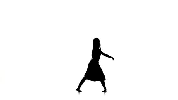 Slim woman dancer dancing contemporary dance, turns around, on white, silhouette, slow motion