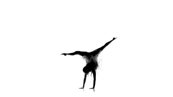 Slim girl with ponytail dance modern contemporary style makes bridge and sits on white, silhouette, slow motion