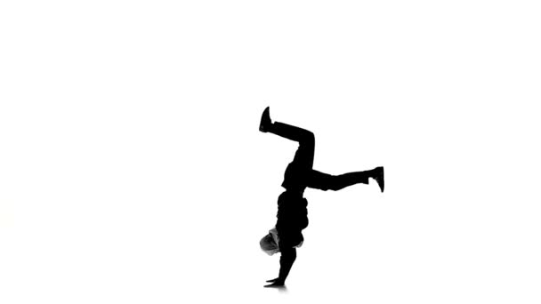 Young man dancing breakdance on hands, white, silhouette, slow motion