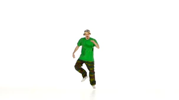 Dancer in green shirt dancing breakdance, makes movement, white, slow motion