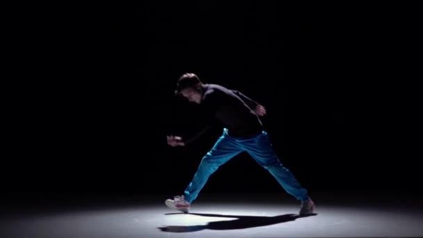 Moderní rozlámaný muž v modrých kalhotách tanec, černý, stín, pomalý pohyb