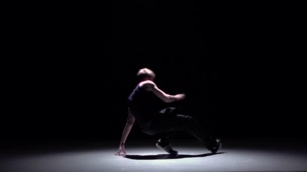 Talanted blonde dancer starts dancing breakdance, on black, shadow, slow motion