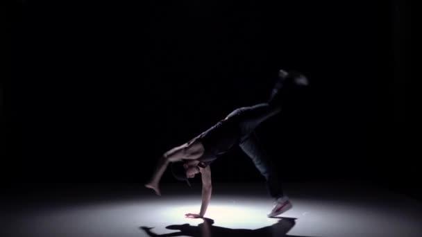 Talanted dancer man dancing breakdance on black, shadow, slow motion