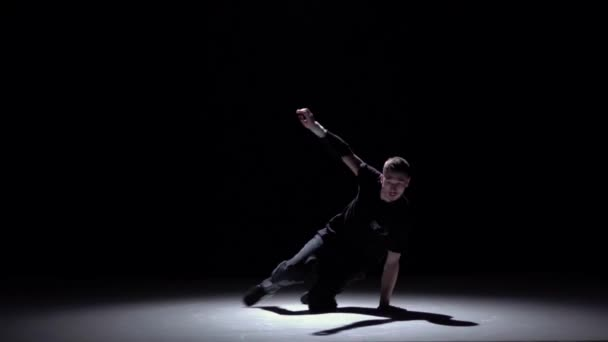 Cool breakdance style dancer starts dance, on black, shadow, slow motion