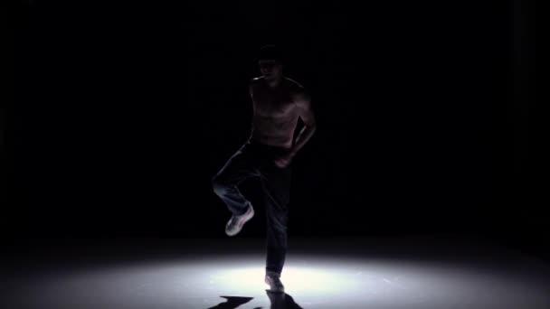 Breakdance táncos férfi nadrágban, sapka meztelen törzs tánc fekete, árnyék, lassított