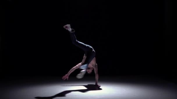 Breakdancer man in cap doing handstand on black, shadow, slow motion