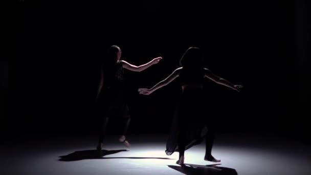 Půvabná současný tanec dvou tanečnic na černou, stín, zpomalené