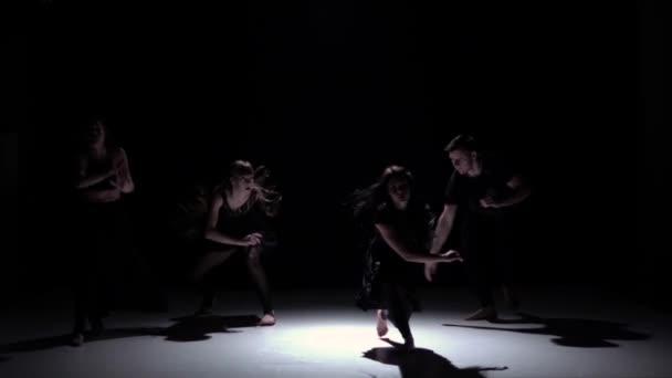 Moderní taneční vystoupení čtyř tanečníků přes černou, stín, zpomalené