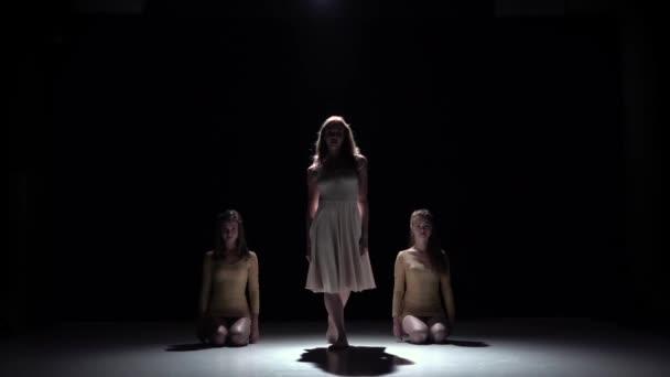 Beginn des zeitgenössischen Tanzes von drei Mädchen in weißen Kleidern, auf Schwarz, Schatten, Zeitlupe
