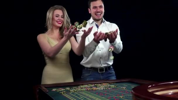 Winnings couple throwing chips in the air. Black