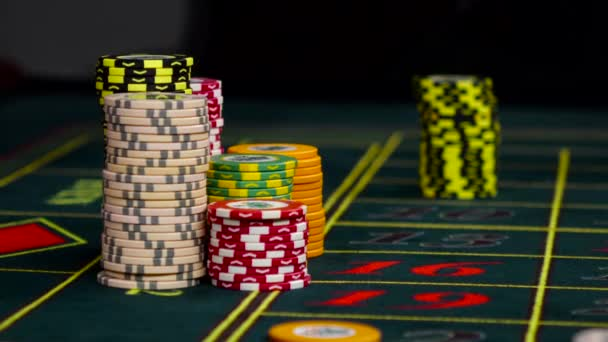Croupier bets chips on roulette green table at casino, black