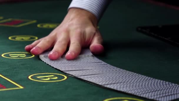 Croupier shuffling poker playing cards on green table, slow motion