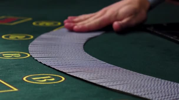 Croupier mixing cards, shows one on green table at casino