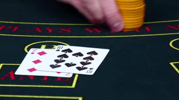 Player bets chips on poker table with cards, slow motion