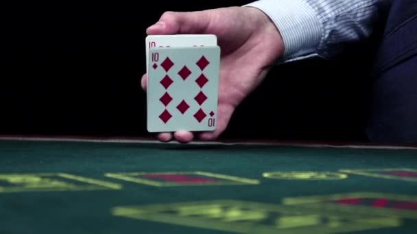 Croupie šourání obvyklých pokerové karty na stole, černý, pomalý pohyb