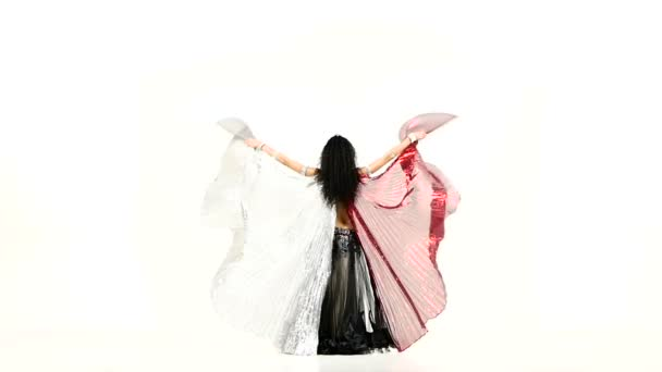 Exotic belly dancer with two wings, in unusual suit dance, on white, slow motion