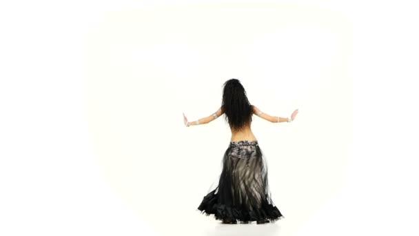 Bauchtänzerin Brünette Frau in dunklem und beigem Kostüm tanzt und wirbelt, auf weißem, Zeitlupentempo