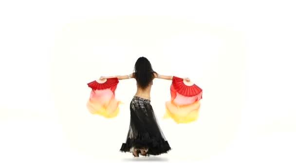 schlanke Bauchtänzerin tanzt mit langen Fächern, wedelt mit den Haaren, schüttelt die Hüften, auf weiß, Zeitlupe