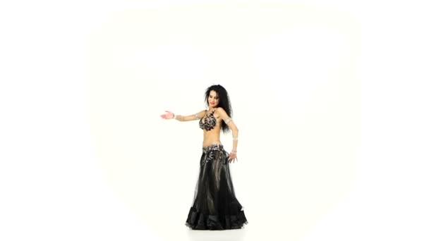 schöne schlanke Bauchtänzerin mit dunklen Haaren, die tanzt und ihre Hüften schüttelt, auf weißem, Zeitlupentempo