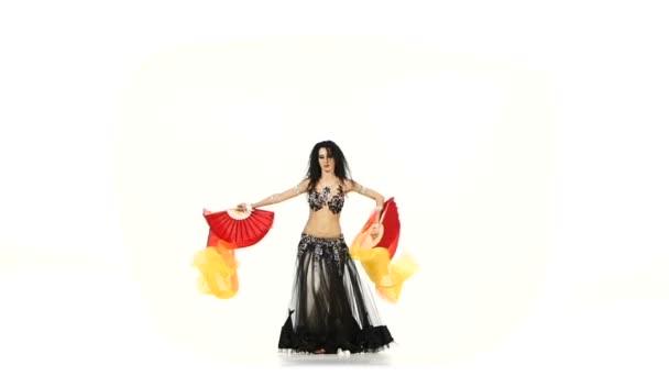 talanted, lockiges Bauchtänzermädchen tanzt mit zwei langen Fächern, schüttelt die Hüften, auf weißer Zeitlupe