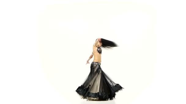 Bauchtänzerin Frau in dunklem und beigem Kostüm tanzt und wirbelt, auf weißem, Zeitlupentempo