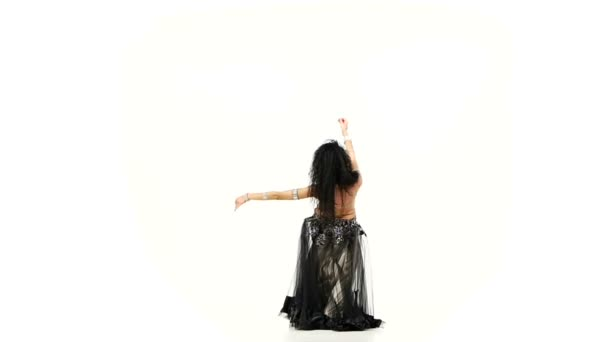 exotisch schöne Bauchtänzerin mit langen dunklen Haaren, die ihre Hüften schütteln, beugt sich, auf weiß, Zeitlupe