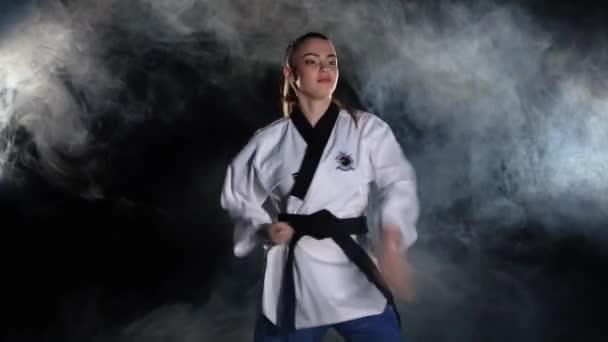 Karate kick girl in kimono practice technical shots. Black