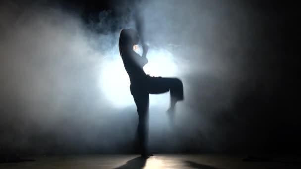 Lány izmos test. Képzés harcművészetek. Fekete. Sziluett. Háttérvilágítás